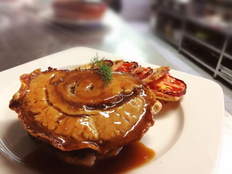 """La nostra """"porchetta"""": cansalada confitada i rostida, milfulles de patata i tomàquet, compota de poma i el suc del seu rostit."""